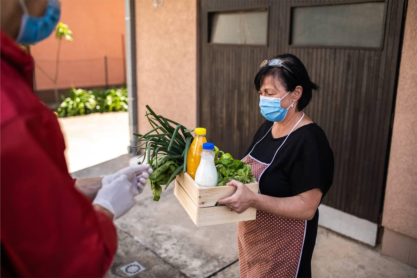 woman carrying carton of food