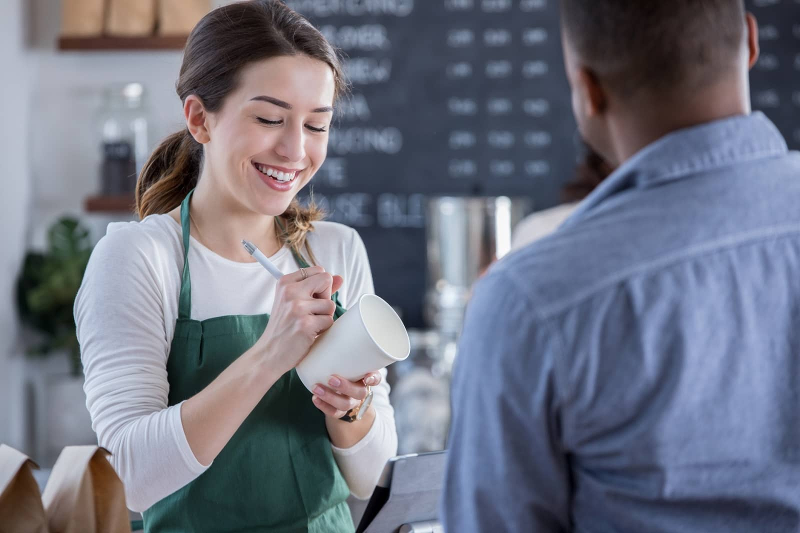 Cheerful coffee shop barista writes order on cup