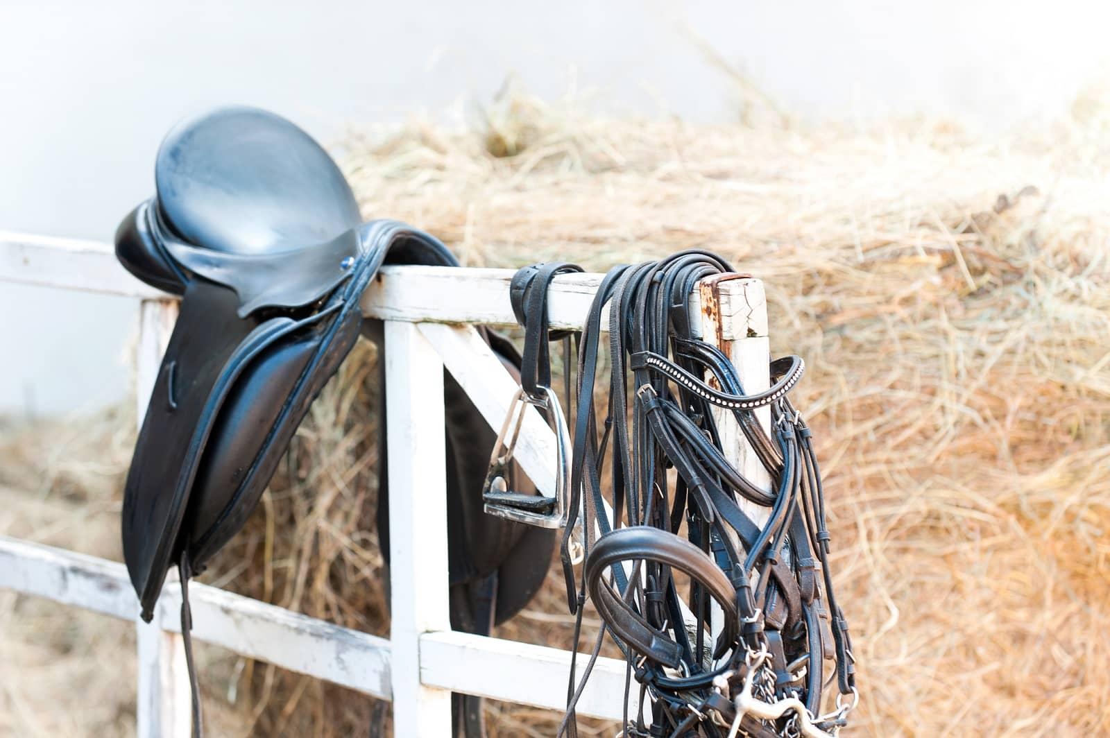 Saddle drapped on fence