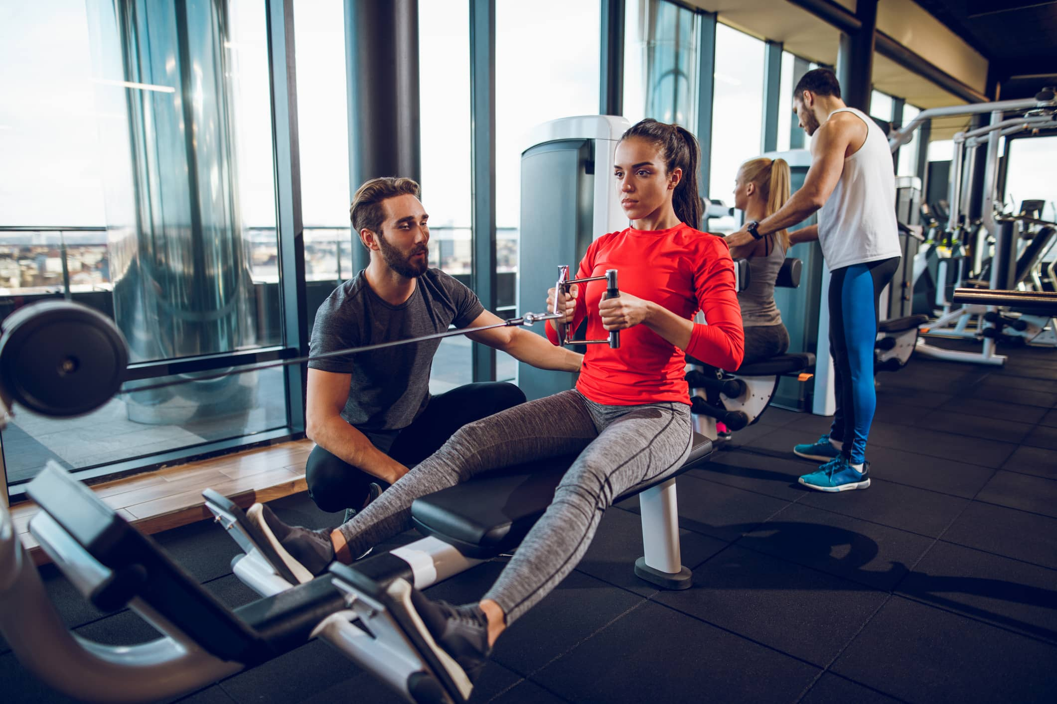 Workout with personal trainer on rowing machine at gym