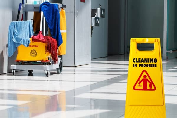 Cleaning in progress sign with janitor cart