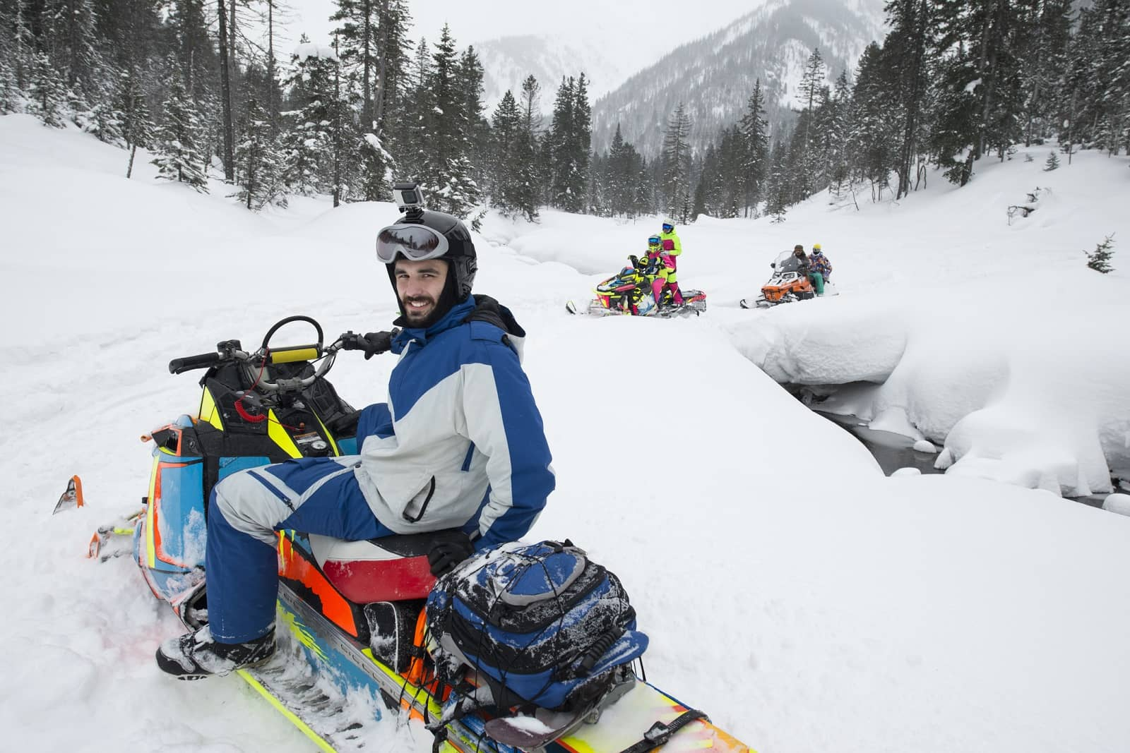 Snowmobilers riding through forest