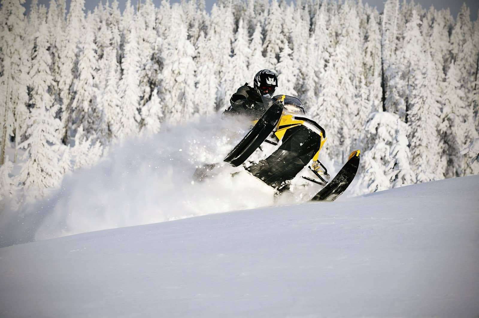Snowmobile jumping through powdery snow