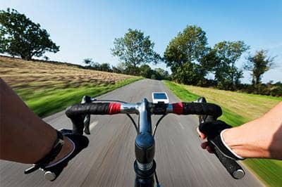 View of bicycle handle bars riding down open road