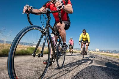 Group of cyclists riding on open road