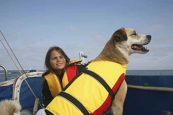 Dog wearing life jacket on boat with girl