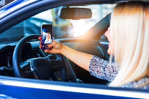 Woman in car taking selfie