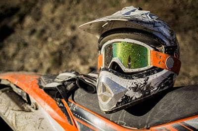 muddy helmet and goggles on ATV seat