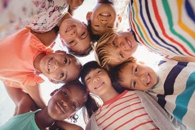 Kids huddled together smiling