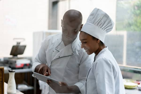Cooks at a restaurant looking at the menu on a tablet computer