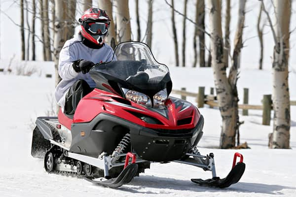 Person driving red and black snowmobile