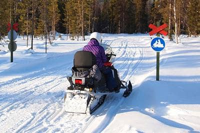 Driving snowmobile past snowmobile crossing sign